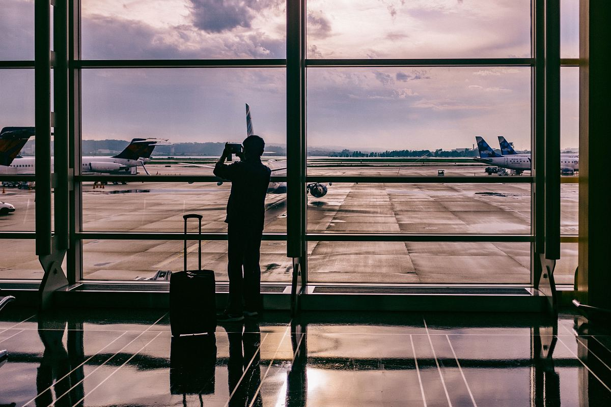 stock photos free  of silhouette of person standing in front of glass while taking photo of plane
