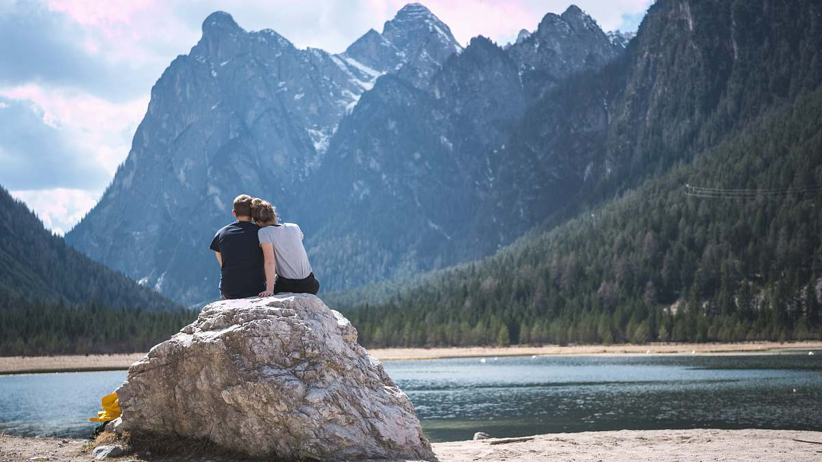 stock photos free  of people man and woman sitting on rock near body of water and mountain during daytime couple