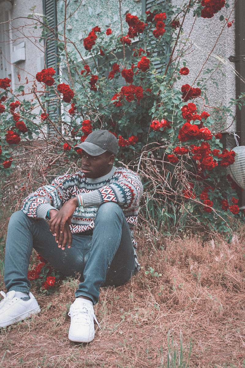 stock photos free  of human man sitting on grass in front of red flowered plant person