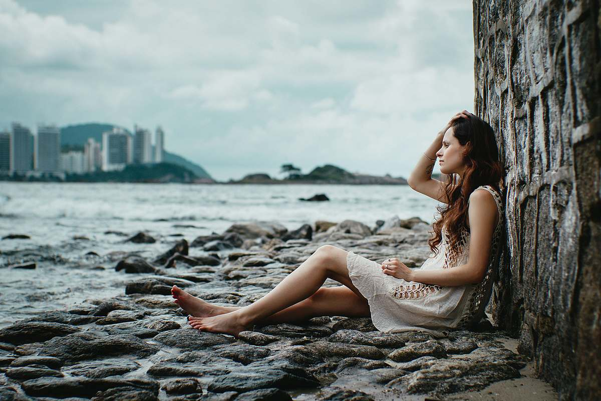 stock photos free  of person woman leaning on stone wall near body of water human
