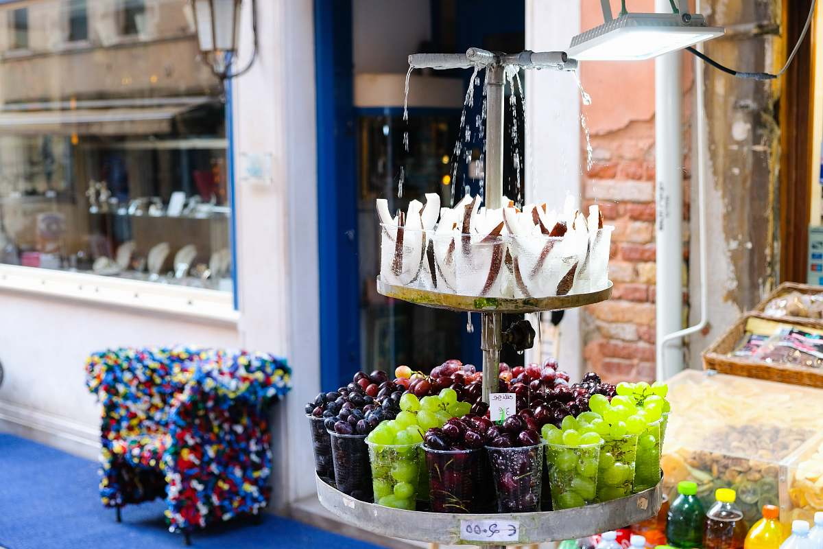 stock photos free  of sweets displayed fruits outside white and brown building during daytime confectionery