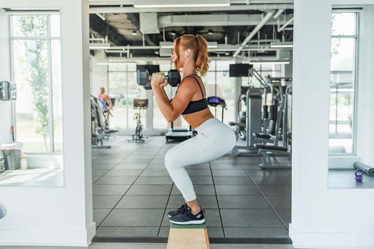 stock photos free  of human woman wearing black sports bra and white legging lifting dummbells sports