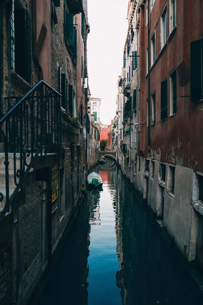 stock photos free  of water white boat on canal in between concrete houses building