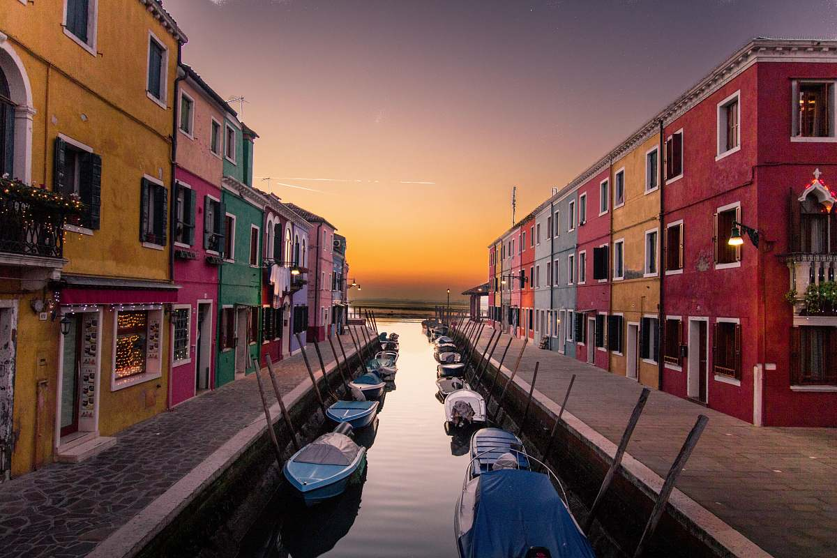 stock photos free  of building blue boats parked on river between multicolored buildings at sunset city