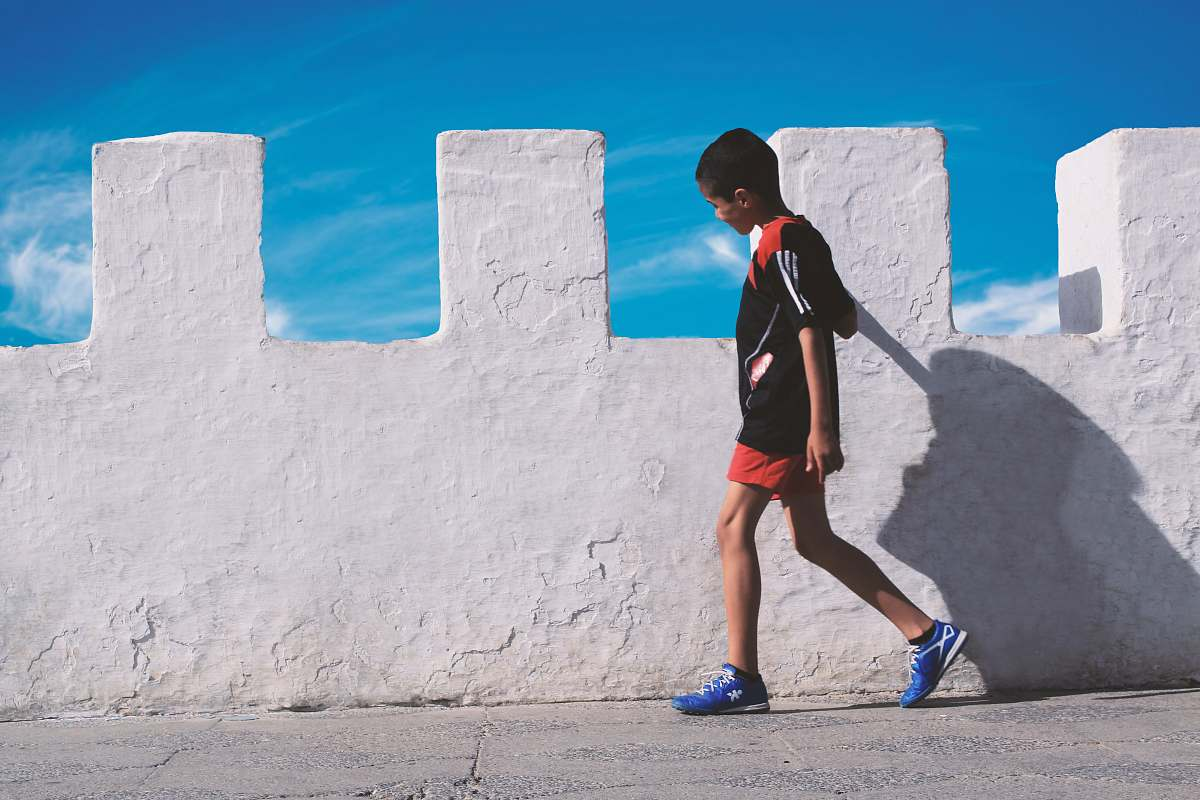 stock photos free  of person boy walking beside white concrete wall people