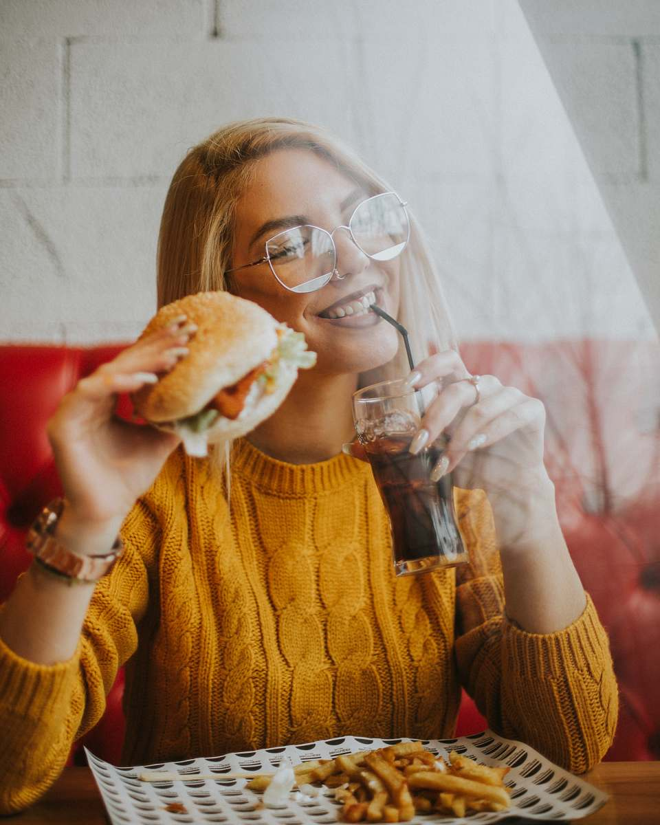 stock photos free  of human woman sitting while holding burger person