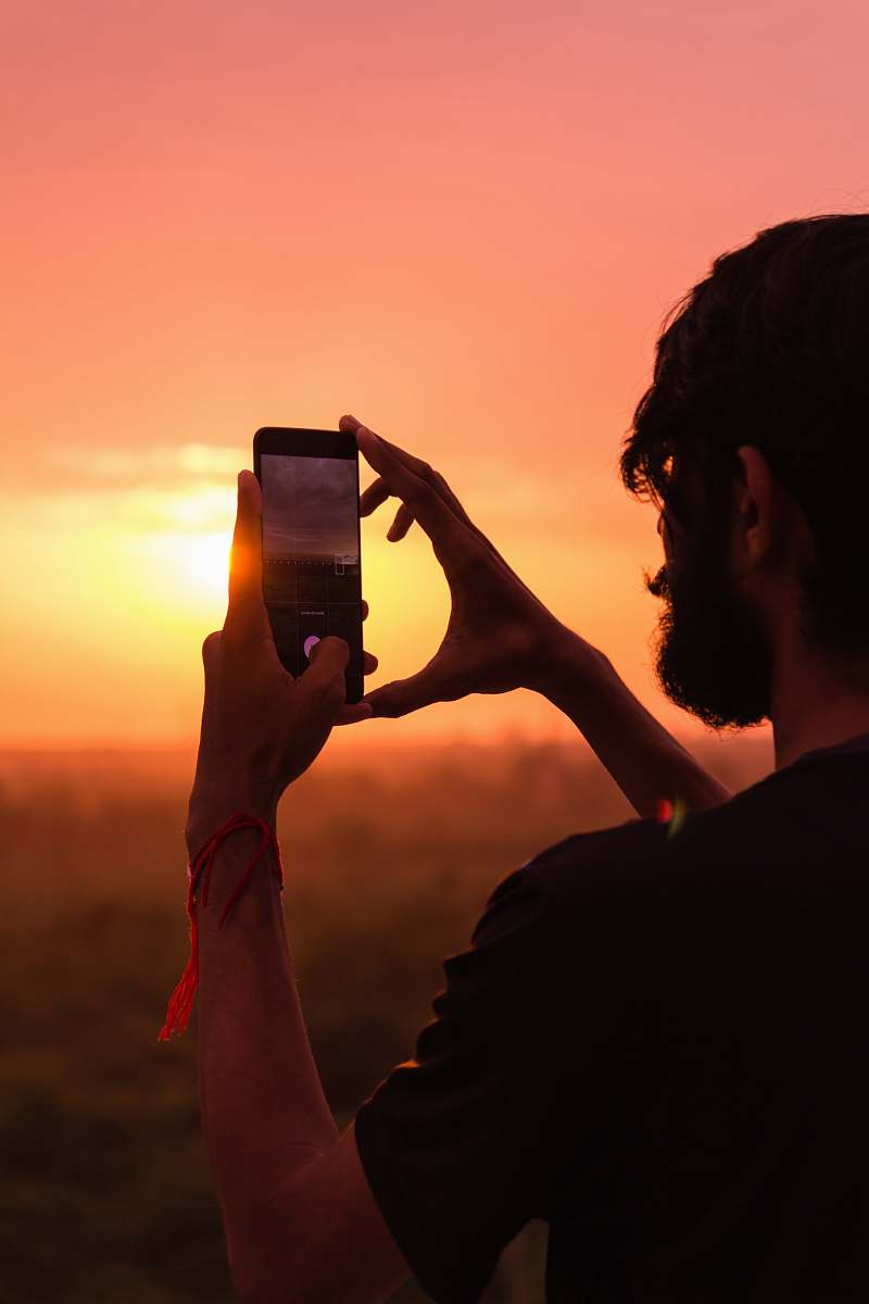 stock photos free  of person man holding smartphone on high ground during golden hour outdoors