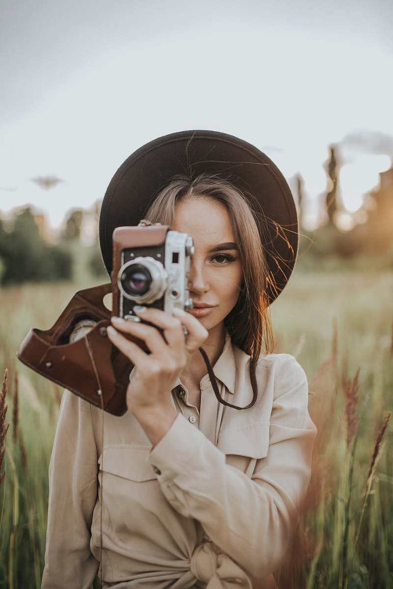 stock photos free  of person woman holding camera in field during daytime camera