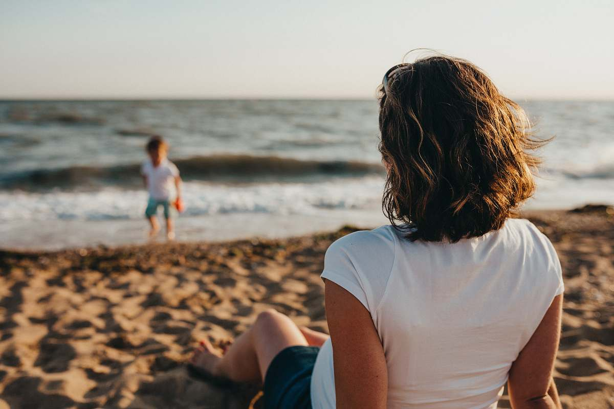 stock photos free  of water woman watching child playing on beach during daytime ocean