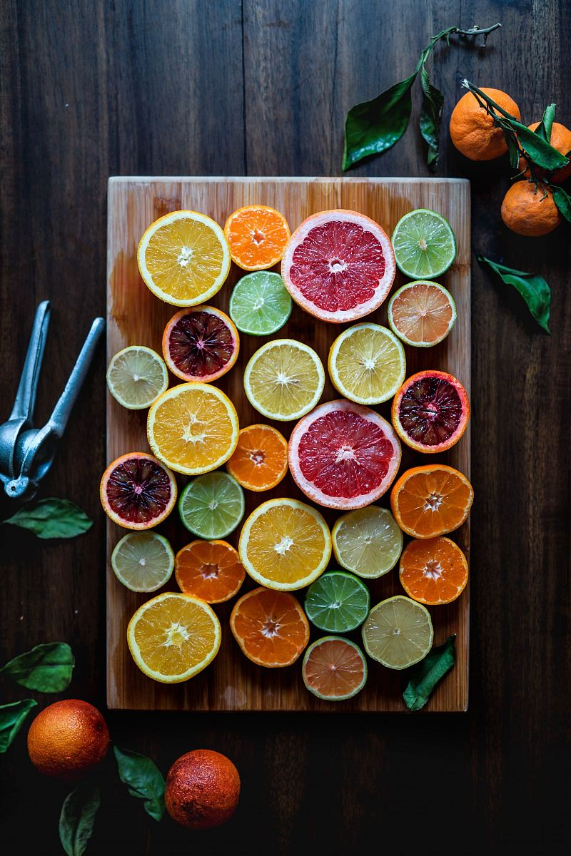 stock photos free  of assorted sliced citrus fruits on brown wooden chopping board