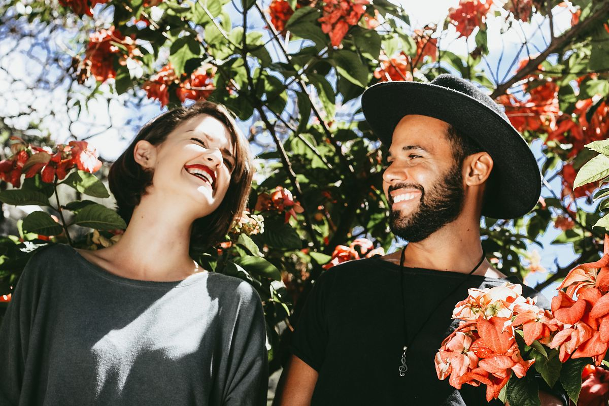 stock photos free  of man and woman surrounded by red and green floral trees during daytime