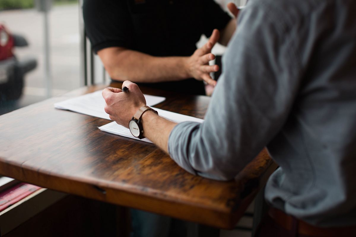 stock photos free  of two person writing on paper on brown wooden table