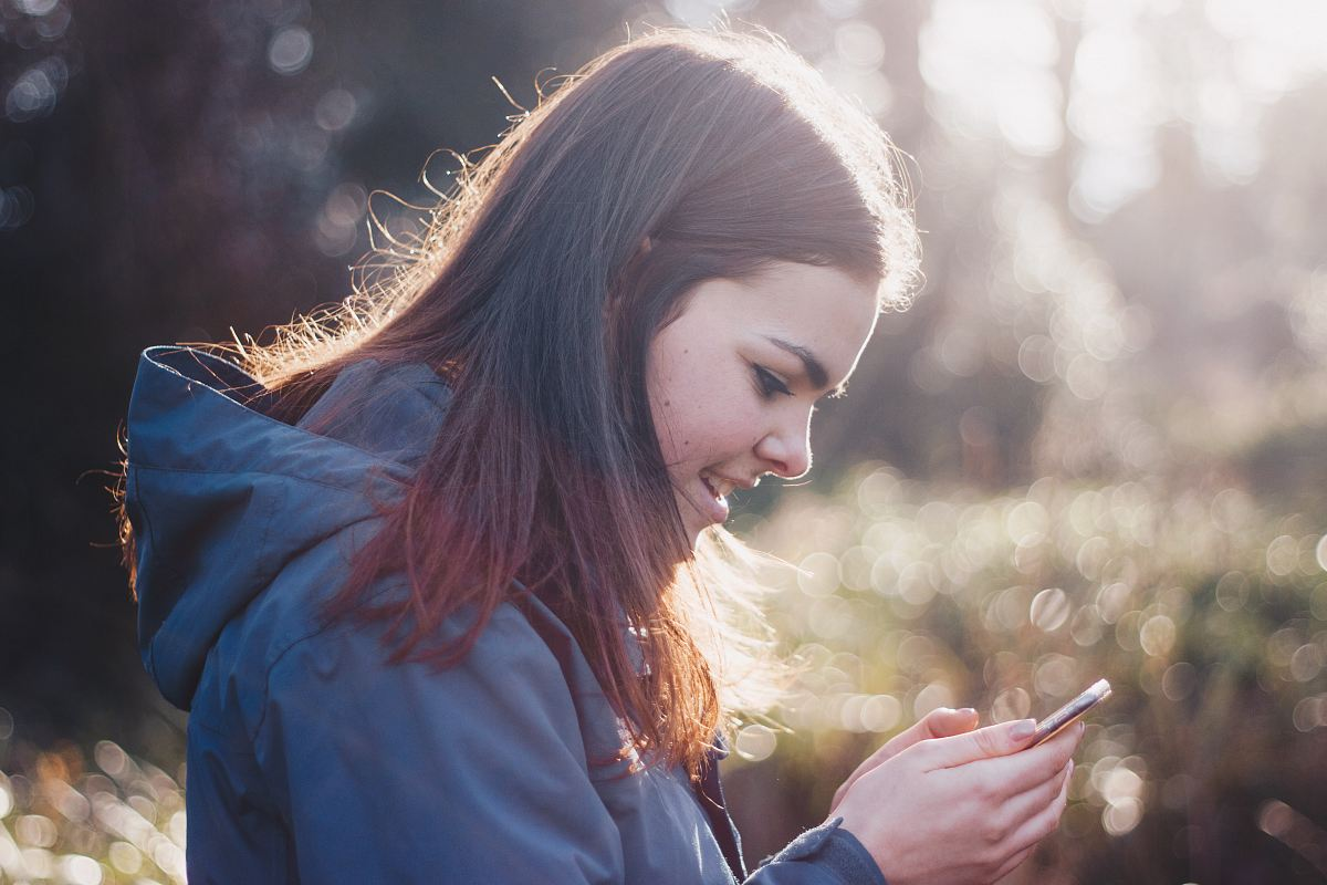 stock photos free  of woman holding phone smiling