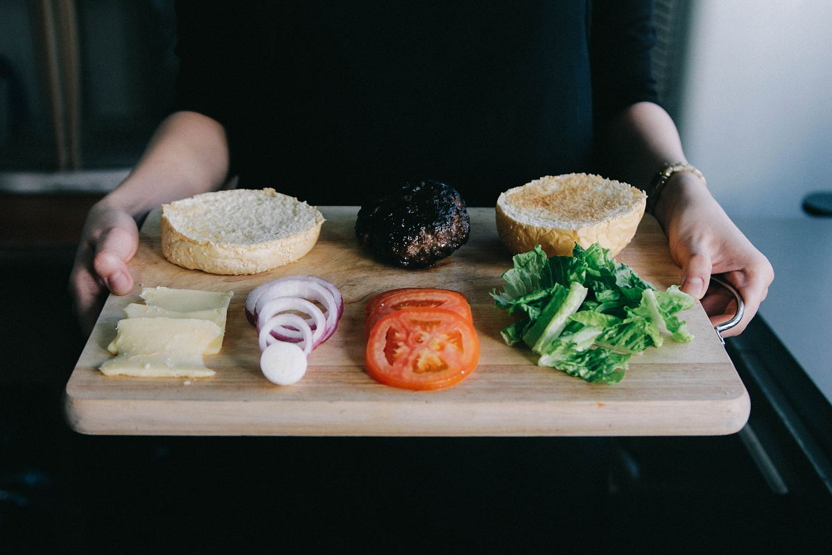 stock photos free  of woman holding up wooden tray with lettuce, tomato, onions rings and cooked patty for burger