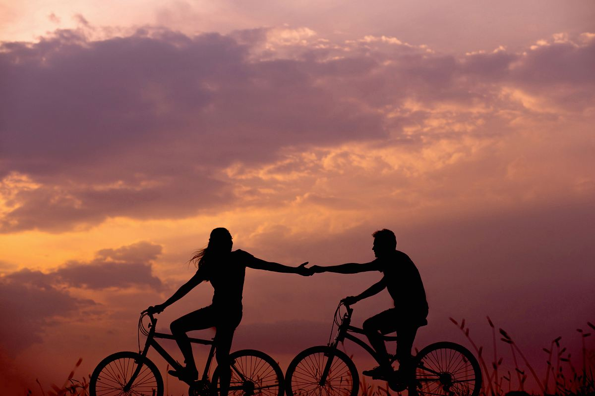 stock photos free  of woman on bike reaching for man's hand behind her also on bike