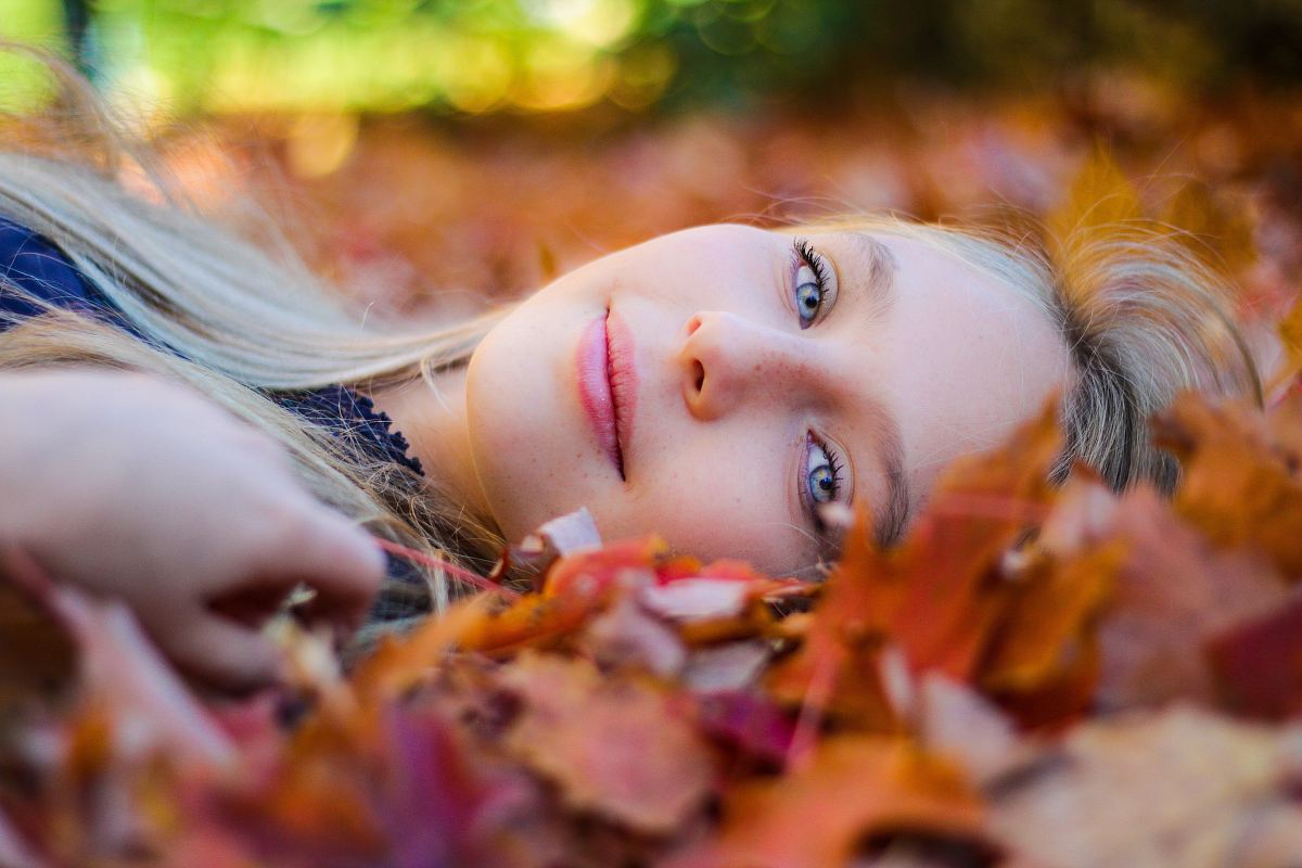 stock photos free  of woman wearing blue top lying on dried maple leaves during daytime photography