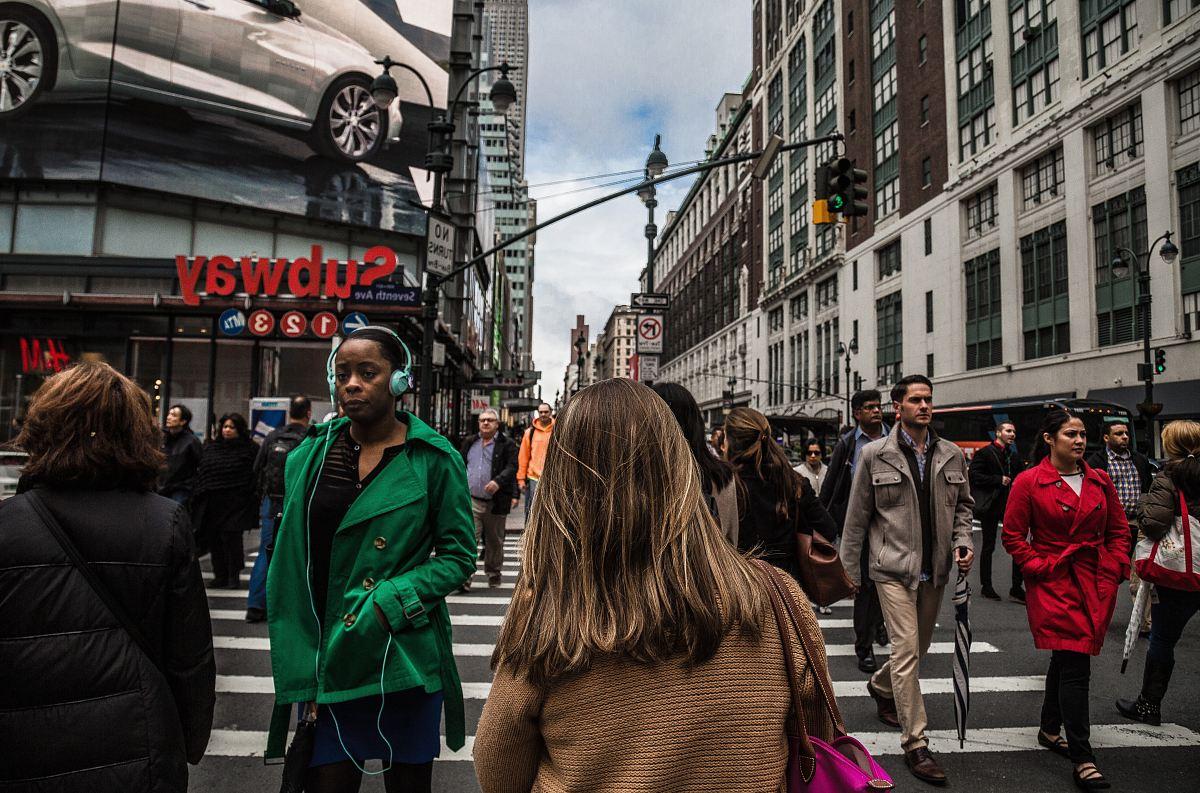 stock photos free  of woman wearing green jacket walking on the pedestrian lane during daytime
