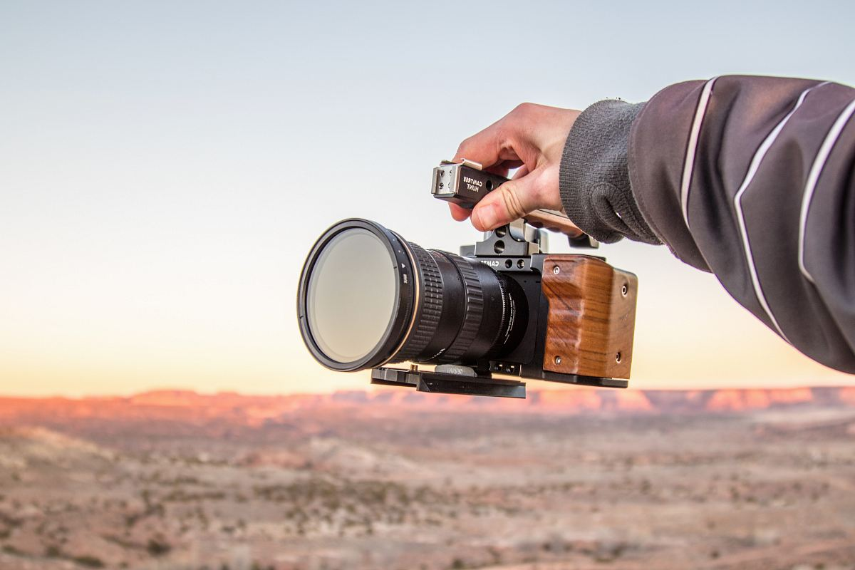 stock photos free  of person holding black DSLR camera