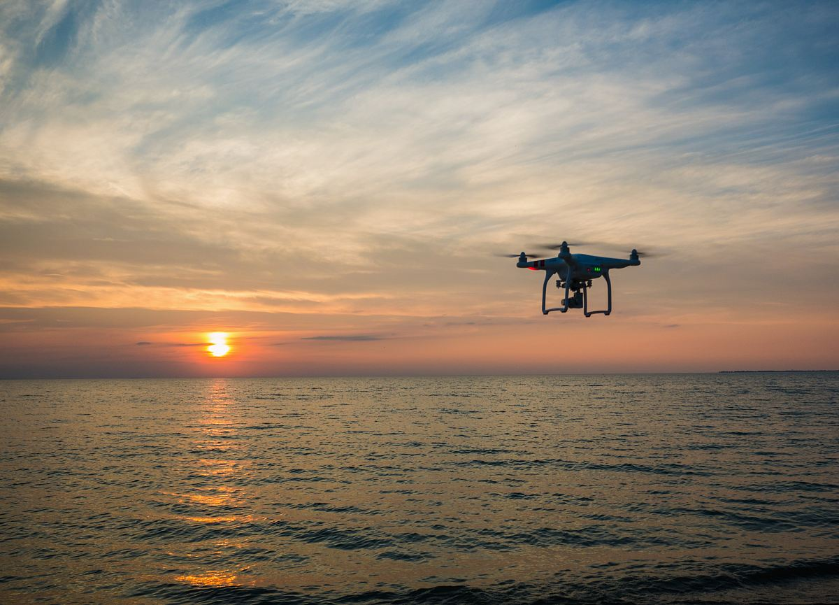 stock photos free  of quadcopter flying over body of water
