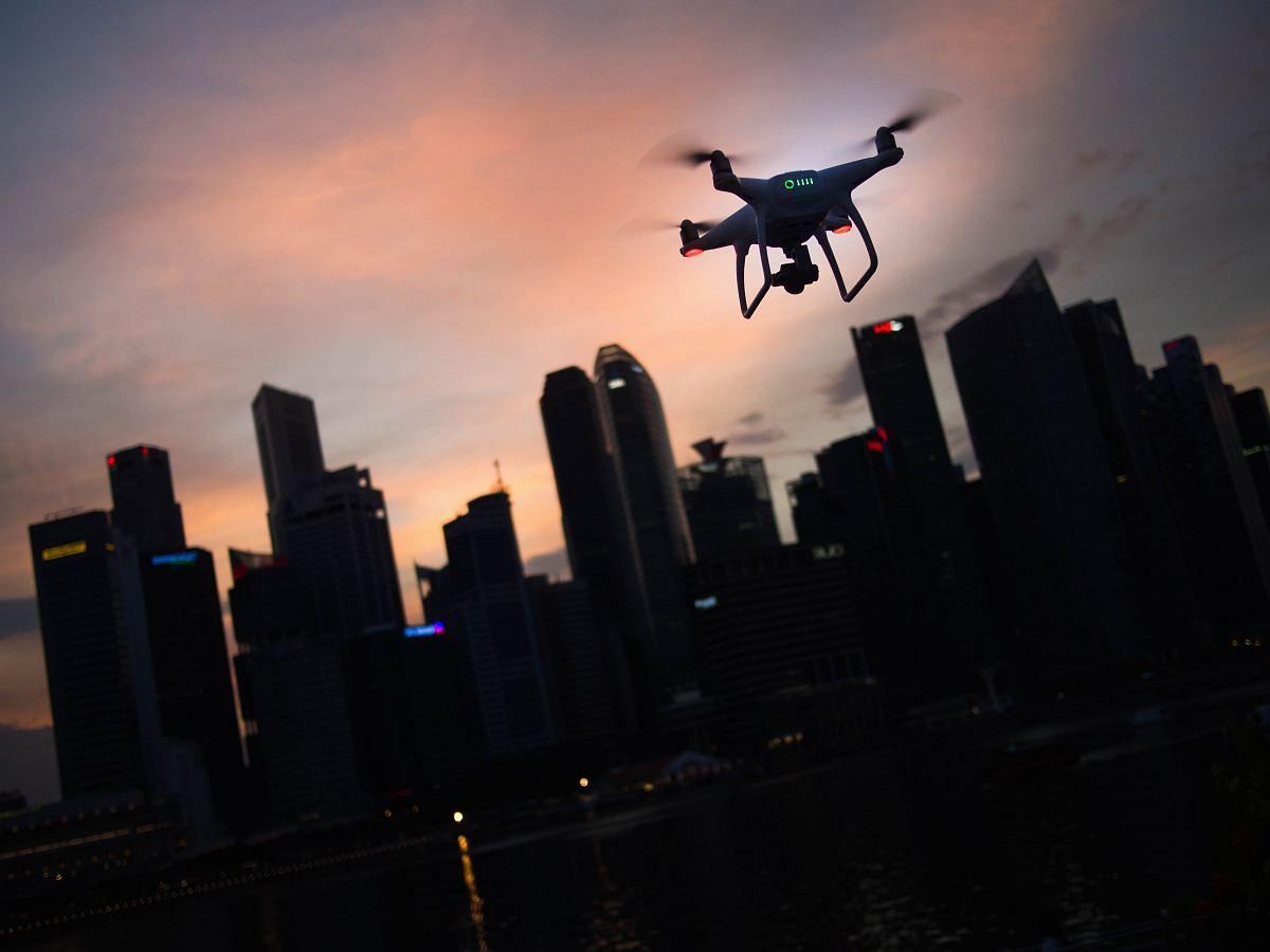 stock photos free  of silhouette of quadcopter drone hovering near the city