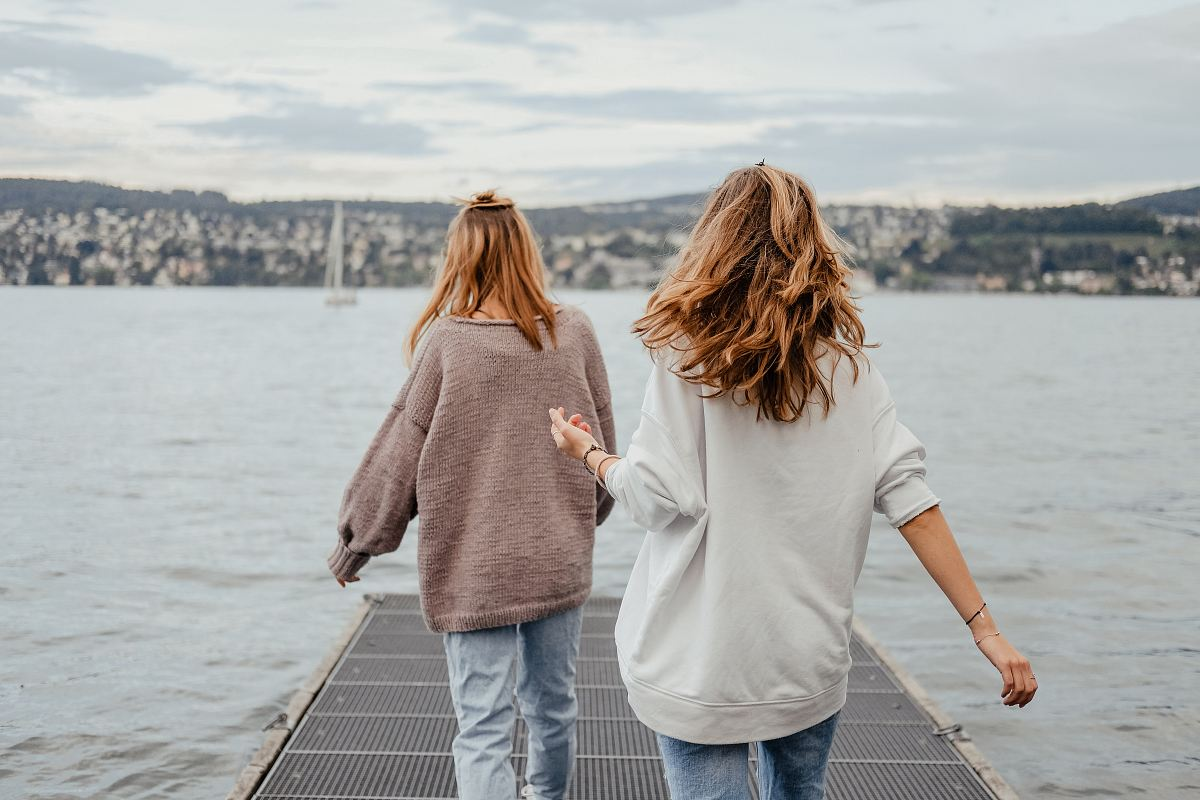 stock photos free  of two women standing on dock front of sea at daytime