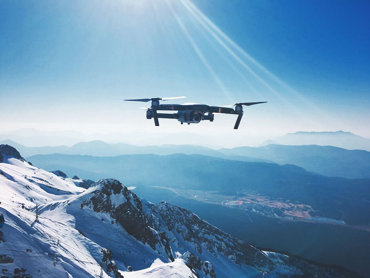 stock photos free  of white quadcopter drone flying near snow mountain during daytime