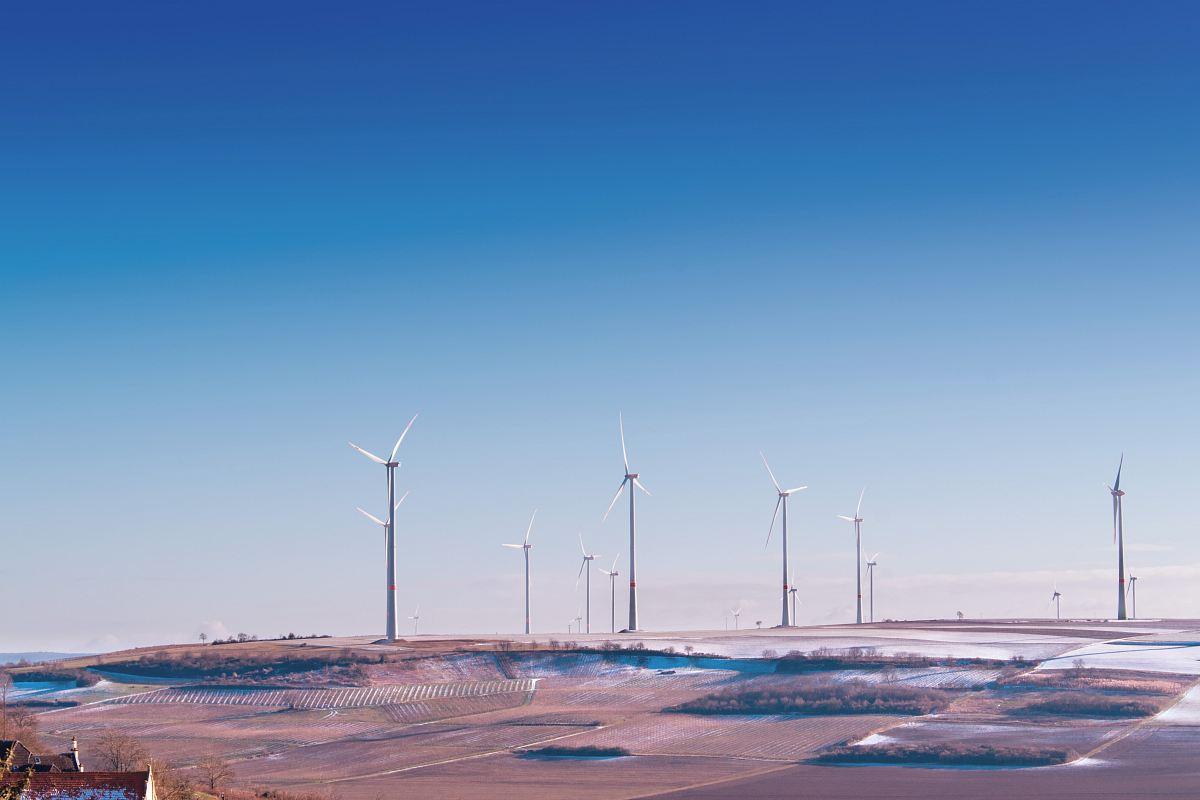 stock photos free  of white wind turbine on grey desert under blue and white sky