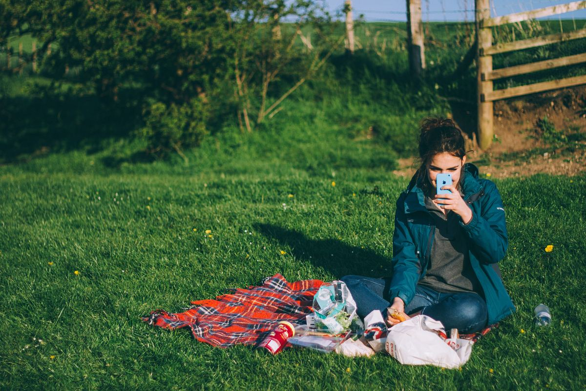 stock photos free  of woman in blue outfit using blue smartphone while sitting on grass