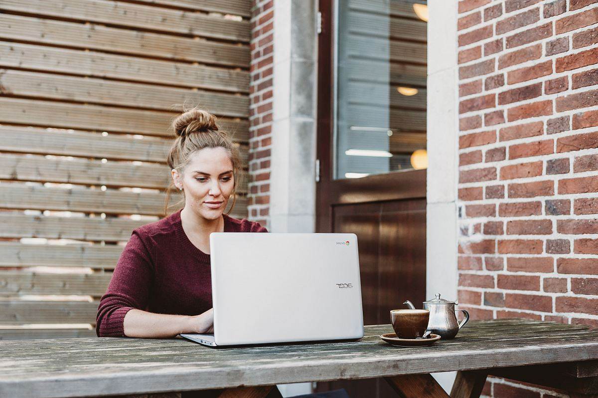 stock photos free  of woman sitting and holding white Acer laptop near brown wooden wall