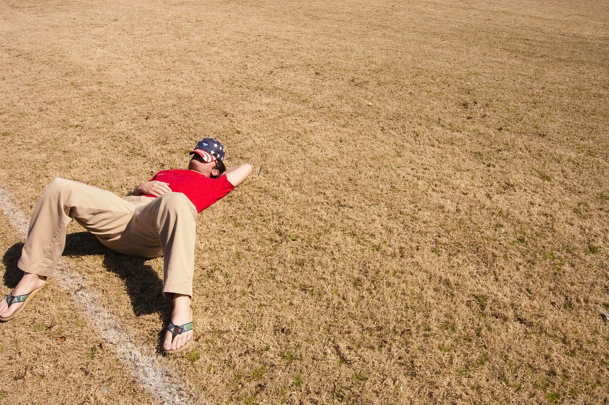 stock photos free  of man in red top lying on lawn field during daytime