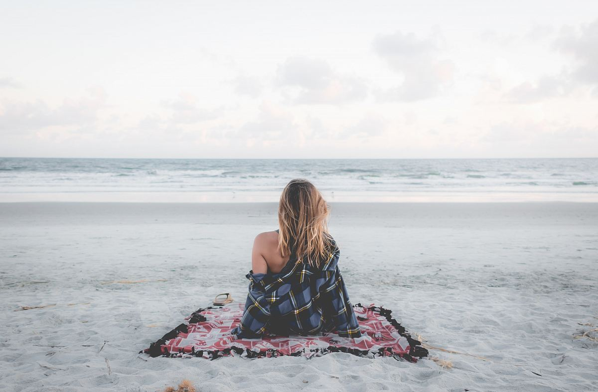 stock photos free  of woman sitting on blanket located on shoreline