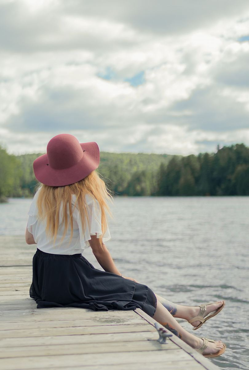 stock photos free  of woman sitting on dock under cumulus clouds