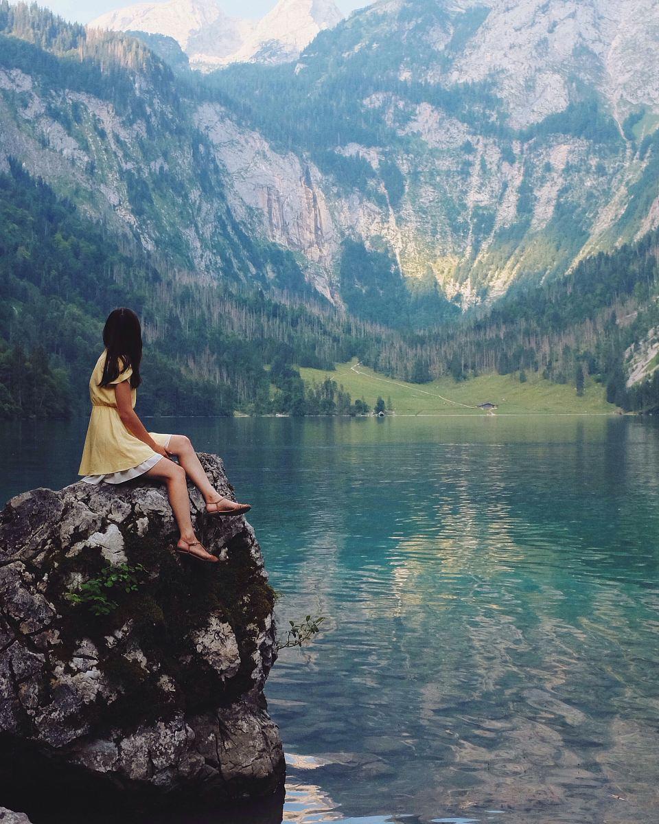 stock photos free  of woman sitting on rock near lake