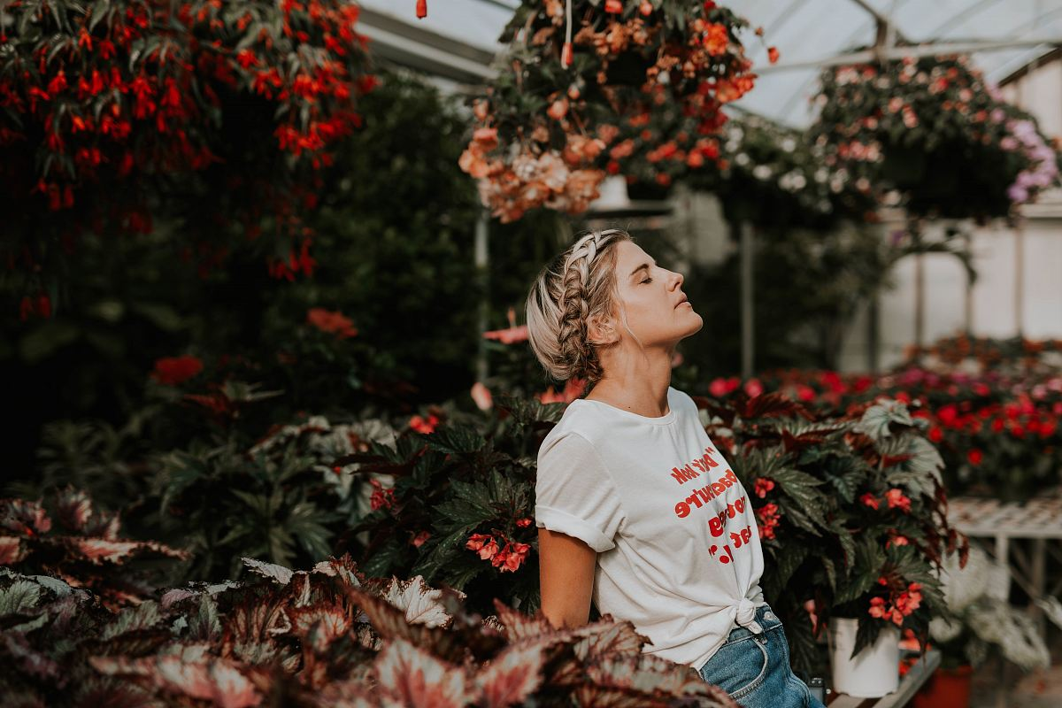 stock photos free  of woman wearing white shirt standing near the flower
