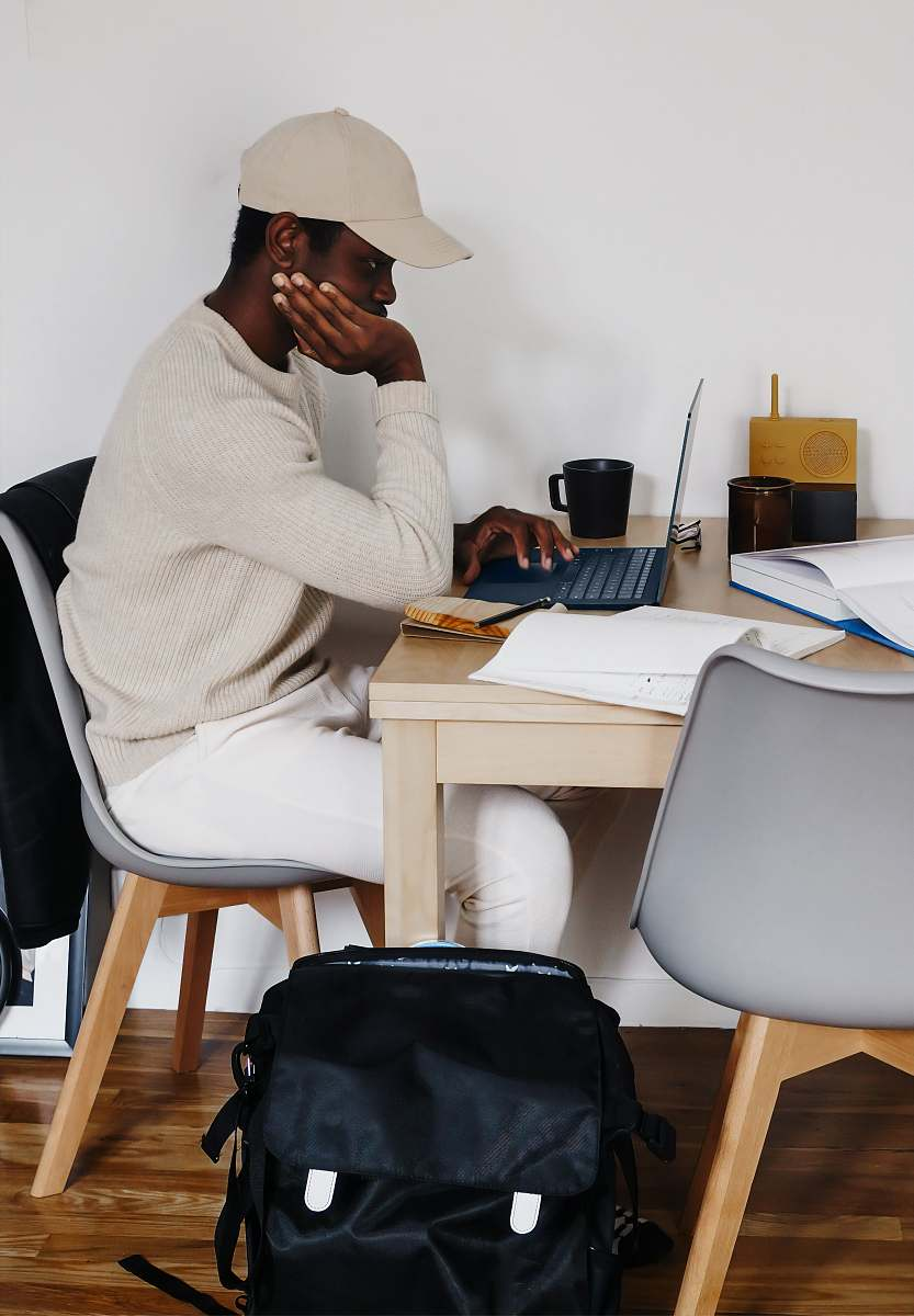 stock photos free  of furniture man in white sweater sitting on chair using Microsoft Surface Laptop 3   table