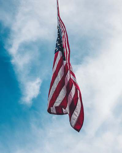 american flag flag of the United State flying under white clouds flag pole