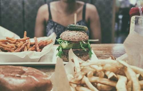 burger burger beside potato fries person