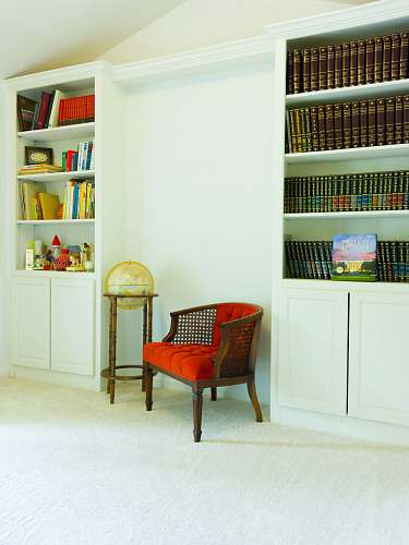 shelf red padded brown wooden armchair beside white wooden shelf bookcase