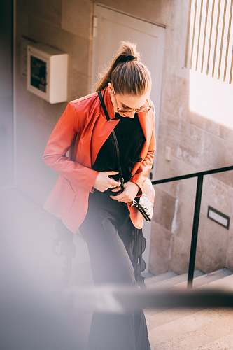 clothing woman wearing orange jacket and black pants with black inner shirts apparel