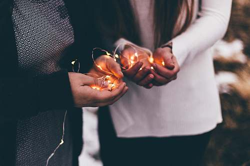 person close-up photo of two person holding lighted string lights sea life