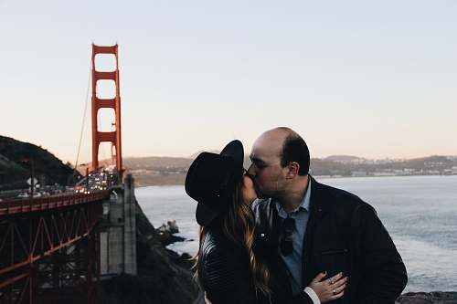 person man and woman kissing beside Golden Gate Bridge during daytime people