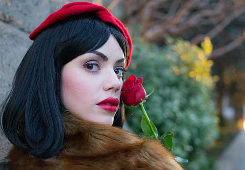 person woman wearing brown coat holding red rose near wall during daytime people