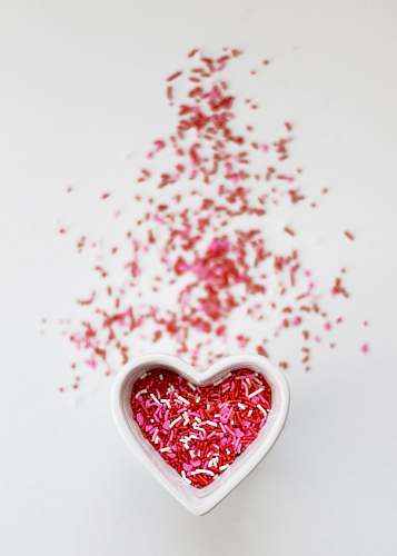valentine selective focus photo ofsprinkles in heart ceramic bowl candy