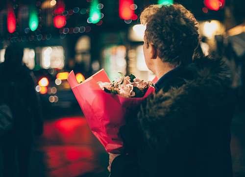 human man in black faux fur coat holding bouquet of floweers people