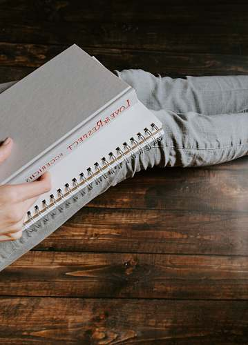 human person holding white notebook text