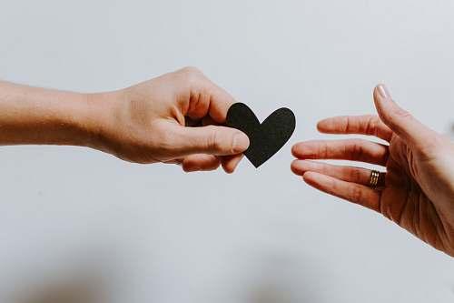 human person reaching black heart cutout paper finger