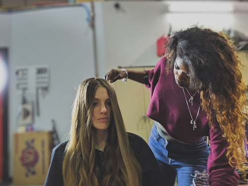 human woman arranging the hair of woman sitting on chair apparel