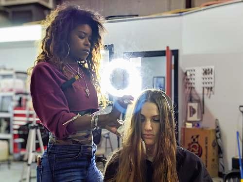 human woman fixing woman's hair apparel