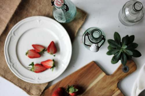 bottle fruits on plate with bottles on white table strawberry