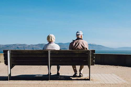 person man and woman sitting on bench facing sea bench
